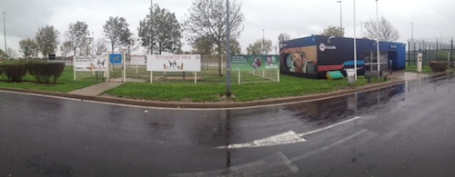 A panorama of the Pet Control Point building and the fenced dog-walking area next to it.