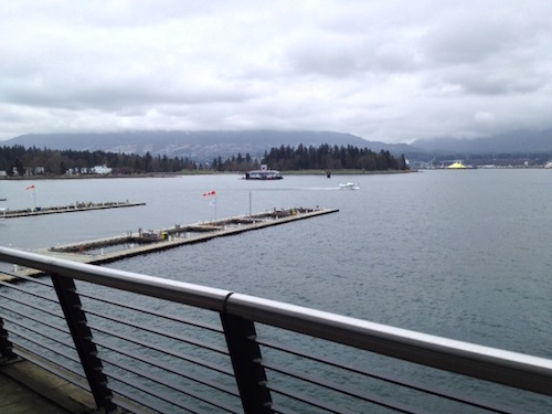 Looking north towards Stanley Park — a seaplane is accelerating towards takeoff over Coal Harbor.