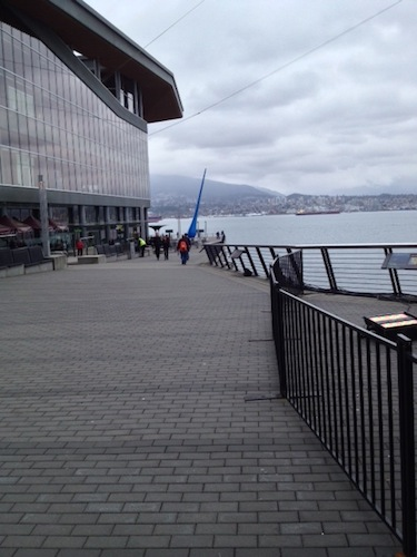 "The beginning of the seawall, just below the conference center (that building looming to the left). The cobbles/bricks are the pedestrian path; bikers have a separate, smooth path on the left. The blue sculpture in the distance is called ""The Drop."""