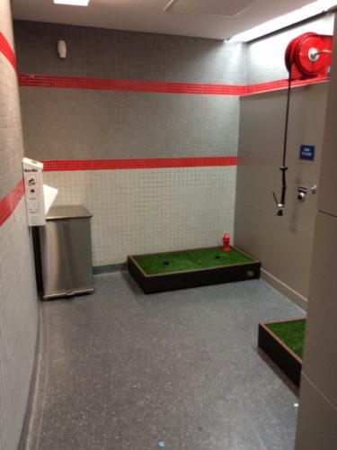 Where the stalls would normally be, however, are two Porch Potty ledges, a trash can, and a poop bag dispenser.