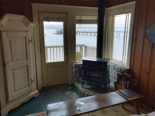 The living room of Al's, with a view of the boat shack past the porch. Please note the wood stove, ready for lighting — a source of much coziness later in the evening.
