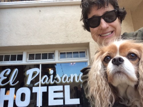 This is the smile of a woman who isn't quite sure that she, her dog, AND the hotel sign are all in the same picture.